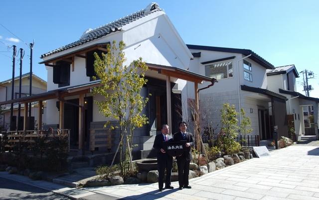 贈呈された土蔵の前で記念撮影に応える高橋努越谷市長(左)と品川典久中央住宅社長
