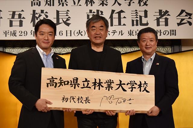 本格開校記念木製看板を掲げる隈研吾氏(中央)、高知県知事尾﨑正直氏(左)ら