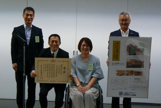 国土交通大臣賞を受賞した北陸リビング社の北出社長と施主の兼氏さん(中央)